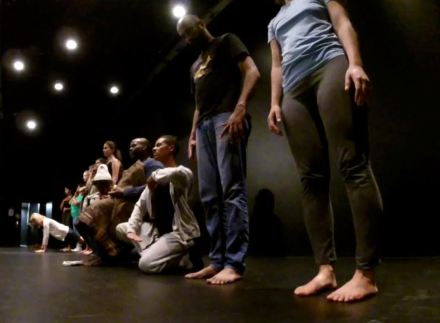 In a dark black box theatre, a line of people stand, sit, kneel. The anle of the photo is taken from low to the ground. People look like living statues, with serious expressions.